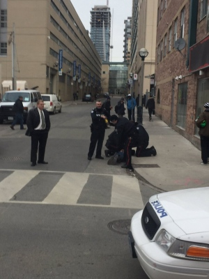 Police are shown arresting a man near Dundas and Church streets on Tuesday morning. (Submitted)