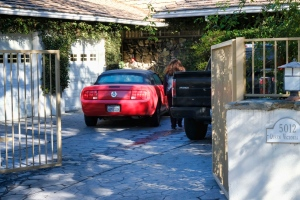An unknown visitor arrives at a gated house in the Woodland Hills section of Los Angeles on Tuesday, Jan. 24, 2017. Homicide detectives are investigating the death of Fabio Sementilli, an internationally known hairdresser and beauty company executive found beaten and stabbed outside his Los Angeles home. Police say paramedics found Sementilli bleeding profusely Monday afternoon at the gated house in the upscale Woodland Hills neighborhood. The 49-year-old suffered multiple stab wounds and died at the scene. (AP Photo/Richard Vogel)