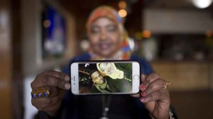 Saciido Shaie, founder and President of the Umma Project holds a picture of herself and close friend Mohamed Badal at a Somali restaurant in Minneapolis, Minn., on Thursday, Feb. 16, 2017. Badal left the United States last week and trekked through the snow covered boarder to get himself into Canada. (Source: Jonathan Hayward/The Canadian Press)