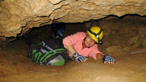 In this July 3, 2008, file photo, New Mexico Tech professor Penny Boston crawls through the Mud Turtle Passage on the way to the Snowy River formation during an expedition in Fort Stanton Cave, N.M. (AP Photo/Susan Montoya Bryan)