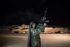 In this Nov. 20, 2016 file photo, a woman fires to the air at a Popular Mobilization Units base south of Mosul, Iraq,. Iraqi troops on Sunday fortified their positions in Mosul neighborhoods retaken from the Islamic State group as their advance toward the city center was slowed by sniper fire and suicide bombings, as well as concern over the safety of civilians. (AP Photo/Felipe Dana, file)