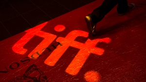 A man walks on a red carpet displaying a sign for the Toronto International Film Festival at the TIFF Bell Lightbox in Toronto on Sept. 3, 2014.  (Darren Calabrese / THE CANADIAN PRESS)