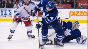 Toronto Maple Leafs defenseman Morgan Rielly (44) clears the puck away from New York Rangers left wing J.T. Miller (10) as Toronto Maple Leafs goalie Frederik Andersen (31) looks on during third period NHL hockey action, in Toronto on Thursday, February 23, 2017. THE CANADIAN PRESS/Chris Young
