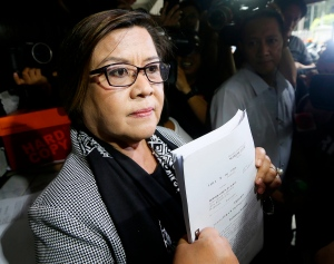 """Opposition Senator Leila De Lima holds documents as she files a petition in the Philippine Supreme Court seeking to stop President Rodrigo Duterte from securing private details about her personal life and using them allegedly to degrade her dignity as a human being, a woman and a senator"""" Monday, Nov. 7, 2016 in Manila, Philippines. (AP Photo/Bullit Marquez)"""