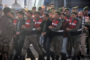 Paramilitary police escort the defendants as a trial opened in Mugla, southern Turkey, Monday, Feb. 20, 2017, for 47 people accused of attempting to kill President Recep Tayyip Erdogan on the night of the failed coup, while he was vacationing with his family. ( DHA-Depo Photos via AP)