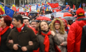 Thousands attend a pro-government rally in Targoviste, Romania, Saturday, Feb. 25, 2017. Supporters of the ruling Social Democratic Party, have joined a pro-government rally, braving pouring rain, in southern Romania, hoping to boost the popularity of the center-left government following massive anti-corruption protests that rocked the country. (AP Photo/David Muntean)