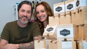 Martin Brouillard and Marie-Eve D'Amico are seen next to a display of Positive Cubes, a small wooden box produced by the Quebec-based company Bangarang Friday, February 24, 2017 in Beloeil, Que. THE CANADIAN PRESS/Paul Chiasson
