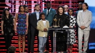"Adele Romanski, at podium, and the cast and crew of ""Moonlight"" accept the award for best feature at the Film Independent Spirit Awards on Saturday, Feb. 25, 2017, in Santa Monica, Calif. (Photo by Chris Pizzello/Invision/AP)"