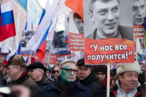 Former Russian Prime Minister, and one of opposition leaders, Mikhail Kasyanov, with his face covered with paint after he was attacked, takes part in a march in memory of opposition leader Boris Nemtsov in Moscow, Russia, Sunday, Feb. 26, 2017. Thousands of Russians take to the streets of downtown Moscow to mark two years since Nemtsov was gunned down outside the Kremlin. The poster reads: We shall overcome! (AP Photo/Ivan Sekretarev)