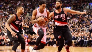 Toronto Raptors guard DeMar DeRozan (10) drives between Portland Trail Blazers guard Damian Lillard (0) and Trail Blazers guard Allen Crabbe (23) during second half NBA basketball action in Toronto on Sunday, February 26, 2017. THE CANADIAN PRESS/Frank Gunn