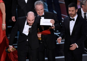 "Jordan Horowitz, producer of ""La La Land,"" shows the envelope revealing ""Moonlight"" as the true winner of best picture at the Oscars on Sunday, Feb. 26, 2017, at the Dolby Theatre in Los Angeles. Presenter Warren Beatty and host Jimmy Kimmel look on from right. (Photo by Chris Pizzello/Invision/AP)"