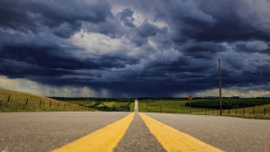 Storm clouds build over a highway in southern Alberta near the town of Carstairs on Monday, July 4, 2016. THE CANADIAN PRESS/Jeff McIntosh