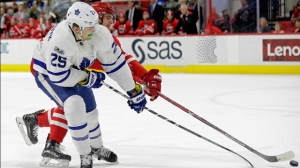 Toronto Maple Leafs' James van Riemsdyk (25) and Carolina Hurricanes' Noah Hanifin chase the puck during the first period of an NHL hockey game in Raleigh, N.C., Saturday, March 11, 2017. Toronto won 3-2. (AP Photo/Gerry Broome)