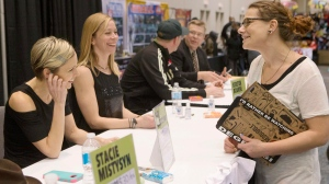 "Former cast members of the television show ""Degrassi"" Stacie Mistysyn, left, and Kirsten Bourne chat to a fan as they make an appearance at Toronto Comicon on Sunday. (Chris Young/The Canadian Press)"