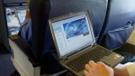 A laptop is used on a plane on July 29, 2002.  (Chris Ison/PA, via AP)