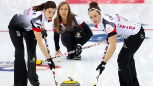 Canada's Lisa Weagle, left, and Joanne Courtney, right, sweep a path for the stone as Rachel Homan, center, watches during their match against Italy in the CPT World Women's Curling Championship 2017 in Beijing on Thursday. (Mark Schiefelbein/AP Photo)