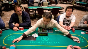 In this Feb. 27, 2013 file photo, dealer Han Kim, center, gathers up chips after a hand of Texas Hold 'em at a poker room in Caesar's Palace in Las Vegas.  Unlike the 2000s when casinos competed to lure fans of the game, poker's appeal has been weakening during this decade. Strip casinos had 405 tables and made $97 million in 2007. In contrast, the game only netted casinos $78 million last year after the number of tables decreased to 320.  (AP Photo/Julie Jacobson, File)