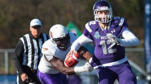 Western Mustangs' quarterback Chris Merchant is grabbed by Laurier Golden Hawks' Kwaku Boateng during first half action in 109th Yates Cup OUA football final in London, Ont. on Saturday, Nov. 12, 2016. THE CANADIAN PRESS/Dave Chidley