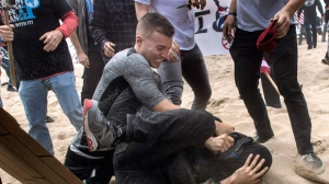 A supporter of President Donald Trump, center, clashes with an anti-Trump protester, bottom center, in Huntington Beach, Calif., on Saturday, March 25, 2017. Violence erupted when a march of about 2,000 Trump supporters at Bolsa Chica State Beach reached a group of about 30 counter-protesters, some of whom began spraying pepper spray, said Capt. Kevin Pearsall of the California State Parks Police. (Mindy Schauer/The Orange County Register via AP)