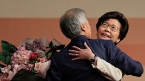 Former Hong Kong Chief Secretary Carrie Lam, right, is hugged by her husband Lam Siu-por after declaring her victory in the chief executive election of Hong Kong in Hong Kong, Sunday, March 26, 2017. A committee dominated by pro-Beijing elites chose Hong Kong's next leader Sunday in the first vote since huge pro-democracy protests erupted over the election system in 2014. (AP Photo/Vincent Yu)
