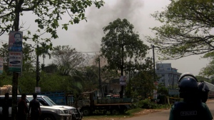 Smoke rises following a blast as Bangladeshi troops try to flush out Islamist radicals who have holed up in a building with a large cache of ammunition in the city of Sylhet, Bangladesh, Sunday, March 26, 2017. At least six people, including two policemen, have died in explosions in eastern Bangladesh as troops battle suspected militants. (AP Photo/A. H. Arif)