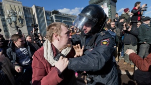 Police officer detains a protester in downtown Moscow, Russia, Sunday, March 26, 2017. Thousands of people crowded into Moscow's Pushkin Square on Sunday for an unsanctioned protest against the Russian government, the biggest gathering in a wave of nationwide protests that were the most extensive show of defiance in years. (AP Photo/Ivan Sekretarev)