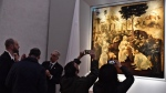 "Visitors take pictures of Leonardo da Vinci's ""Adoration of the Three Wise Men"", returned to the public of the Uffizi museum after 6 years of study and restoration, in Florence, Italy, Monday, March 27, 2017. Painted in 1481, it is one of the most important works of the early Leonardo. (Maurizio Degl' Innocenti/ANSA via AP)"