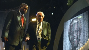 FILE - In this Dec. 15, 2013 file photo, anti-apartheid activist and close friend of Nelson Mandela, Ahmed Kathrada, right, is escorted after speaking at the funeral service for the former South African president, Nelson Mandela, in Qunu, South Africa. Kathrada died Tuesday, March 28, 2017, after a short illness at the age of 87. (AP Photo/Odd Andersen, Pool, File)