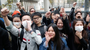 Demonstrators from the Asian community protest outside Paris' 19th district's police station, Tuesday March 28, 2017. Violent clashes in Paris between baton-wielding police and protesters outraged at the police killing of a Chinese man in his home have seen three police officers injured and 35 protesters arrested, authorities said Tuesday. (AP Photo/Michel Euler)