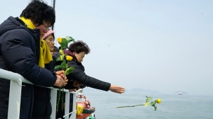 In this photo provided by South Korean Ministry of Oceans and Fisheries, a relative of missing passengers of the sunken Sewol ferry hurls a flower during religious services in waters off Jindo, South Korea, Tuesday, March 28, 2017. South Korean salvage crews on Tuesday found what is presumed to be the remains of one of the missing victims of a 2014 ferry disaster that killed 304 people, an official said. (South Korean Ministry of Oceans and Fisheries via AP)