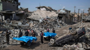 In this Friday, March 24, 2017, file photo, residents carry the body of several people killed during fighting between Iraq security forces and Islamic State militants on the western side of Mosul, Iraq. Iraqis in the northern city of Mosul are still burying their dead after a U.S. airstrike allegedly killed more than 100 people last week, and rights groups are expressing alarm over a recent spike in civilian deaths. Iraqi officials have defended their conduct in the war against the Islamic State group, and their advice to civilians is to shelter in place as U.S.-backed forces seek to drive the extremists from their last urban stronghold in the country (AP Photo/Felipe Dana)