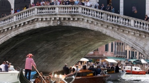 FILE - In this Sept. 26, 2014 file photo, boats pass under the famed Rialto Bridge, in Venice, Italy. Italian police on Thursday, March 30, 2017 arrested three Kosovans in the city of Venice and said one was caught on a phone intercept proposing they bomb the Rialto bridge. (AP Photo/Luca Bruno, files)