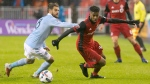 Toronto FC's Raheem Edwards, right, turns around Sporting Kansas City's Graham Zusi during first half MLS action in Toronto on Friday, March 31, 2017. THE CANADIAN PRESS/Chris Young