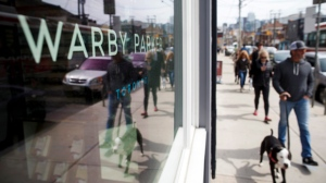 People walk by U.S. based eyewear boutique Warby Parker's flagship Toronto store on Queen St., in Toronto on Sunday, April 9, 2017. THE CANADIAN PRESS/Cole Burston