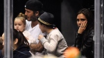 In this Saturday, April 12, 2014 file photo, David Beckham, second left, sits with his daughter, Harper, son, Cruz, and wife Victoria, watch the Los Angeles Kings play the Anaheim Ducks in Los Angeles. (AP Photo/Mark J. Terrill, file)