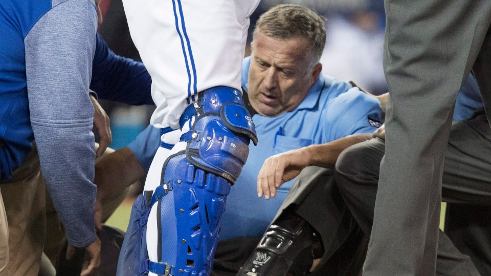 Home plate umpire Dale Scott is attended to on the field in the eighth inning after he was hit by a foul tip during an AL baseball game between the Toronto Blue Jays and the Baltimore Orioles in Toronto. (Fred Thornhill/The Canadian Press)