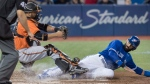 Toronto Blue Jays' Jose Bautista scores getting his foot on home plate before Baltimore Orioles catcher Welington Castillo can come down with the tag in the seventh inning of AL baseball action in Toronto on Saturday April 15, 2017. THE CANADIAN PRESS/Fred Thornhill