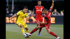 Toronto FC defender Justin Morrow (2) kicks the ball away from Columbus Crew midfielder Niko Hansen (28) during the first half of an MLS soccer match Saturday, April 15, 2017, in Columbus, Ohio. (Fred Squillante/Columbus Dispatch via AP)