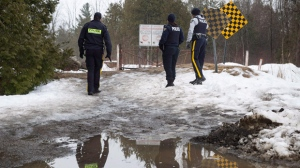 Three RCMP officers look over to the United States on the border with Canada where many asylum seekers have been crossing the United States, Tuesday, March 28, 2017 near Hemmingford, Que. THE CANADIAN PRESS/Paul Chiasson