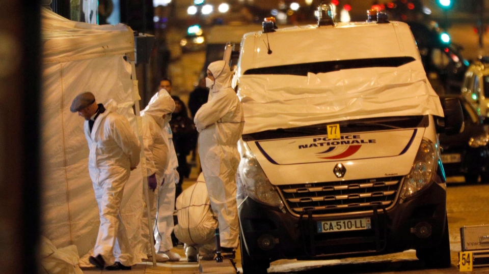 Forensic experts investigate the crime scene after a fatal shooting in which a police officer was killed along with an attacker on the Champs Elysees avenue in Paris. (Kamil Zihnioglu/AP Photo)