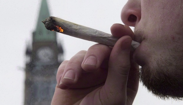 A man lights a marijuana joint as he participates in the 4/20 protest on Parliament Hill in Ottawa, April 20, 2015. (Adrian Wyld / THE CANADIAN PRESS)