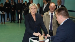 Far-right leader and candidate for the 2017 French presidential election Marine Le Pen casts her vote for the first-round presidential election while National Front Henin-Beaumont's mayor Steeve Briois, second right, looks on, in Henin-Beaumont, northern France, Sunday, April 23, 2017. French voters are casting ballots for their next president in an unusually close first-round election Sunday, after a campaign dominated by concerns about jobs and immigration and clouded by security fears following a recent attack on police guarding the Champs-Elysees in Paris. (AP Photo/Frank Augstein)