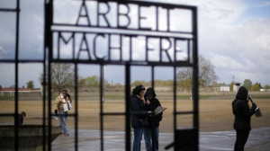People stand behind the gate with the inscription 'Arbeit macht frei' (work sets you free) at the Sachsenhausen Nazi death camp in Oranienburg, about 35 kilometer north of Berlin Sunday, April 23, 2017. Commemorations will be held on Sunday on the occasion of the 72th anniversary of the liberation of the camp. (AP Photo/Markus Schreiber)