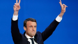 French centrist presidential candidate Emmanuel Macron waves before addressing his supporters at his election day headquarters in Paris , Sunday April 23, 2017.  (AP Photo/Christophe Ena)