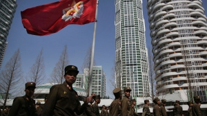 In this April 13, 2017, photo, North Korean soldiers carry the Korean People's Army flag as they walk past residential buildings along Ryomyong street, in Pyongyang, North Korea. (AP Photo/Wong Maye-E)