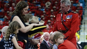 RCMP Commissioner Bob Paulson (right) hugs Const. Douglas Larche's daughter Alexa after presenting the slain RCMP officer's Stetson to widow Nadine (left) as her other daughters Lauren and Mia look on at a regimental funeral for the three slain officers in Moncton, N.B., Tuesday, June 10, 2014. THE CANADIAN PRESS/Sean Kilpatrick