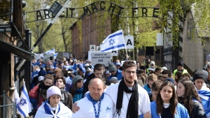 "Participants of the yearly March of the Living walk through the ""Arbeit Macht Frei"" (work sets you free) entrance gate in the former German Nazi Death Camp Auschwitz-Birkenau, in Oswiecim, Poland, Monday, April 24, 2017. Jews from Israel and around the world marched the 3km route from Auschwitz to Birkenau commemorating the Holocaust victims. (AP Photo/Alik Keplicz)"