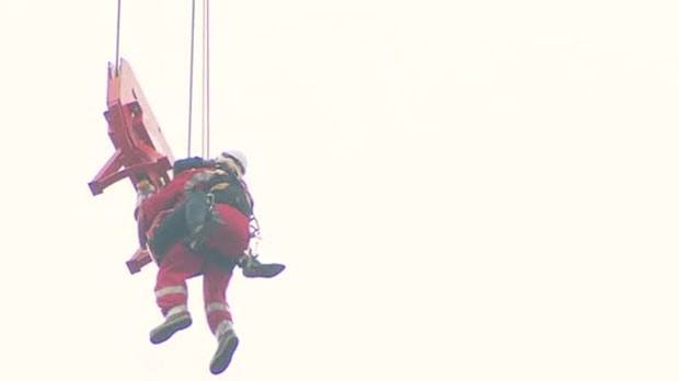 A firefighter and a woman trapped on a crane rappel down near Church and Wellesley streets.