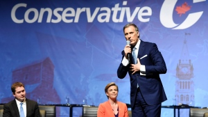 Conservative leadership candidate Maxime Bernier speaks as Andrew Scheer and Kellie Leitch listen during the Conservative Party of Canada leadership debate in Toronto on Wednesday. (Nathan Denette/The Canadian Press)