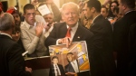 """FILE - In this Jan. 29, 2016, file photo, Republican presidential candidate Donald Trump holds depictions of himself on, """"The Simpsons"""" and a photo with boxer Mike Tyson, given to him by an attendee during a campaign stop at the Radisson Hotel in Nashua, N.H. """"The Simpsons"""" released a short online clip on April 26, 2017, mocking President Donald Trump ahead of his 100th day in office. (AP Photo/John Minchillo, File)"""
